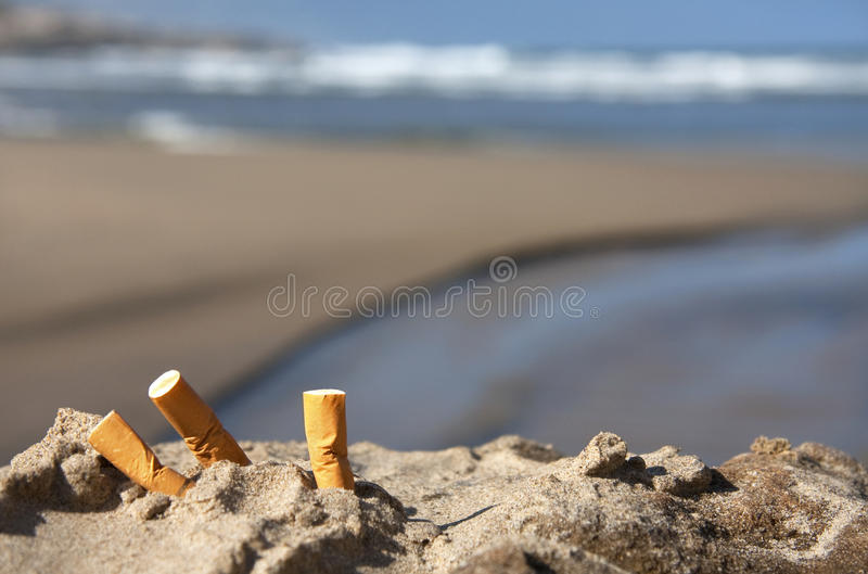 Three cigarette butts on beach. Three cigarette butts in the sand on beach with sea in background stock images