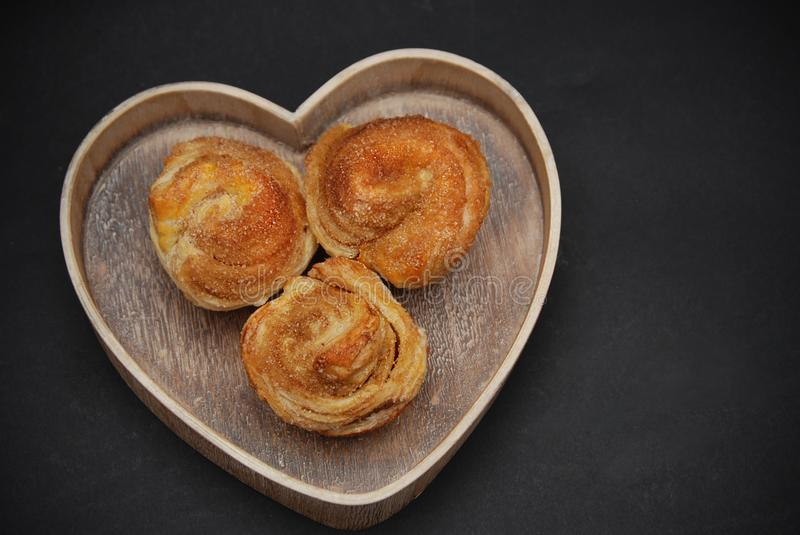 Three Cinnamon Sweet Roll Buns in Wooden Heart, Over the Black background. Love for Desserts and Confectionarry. royalty free stock images