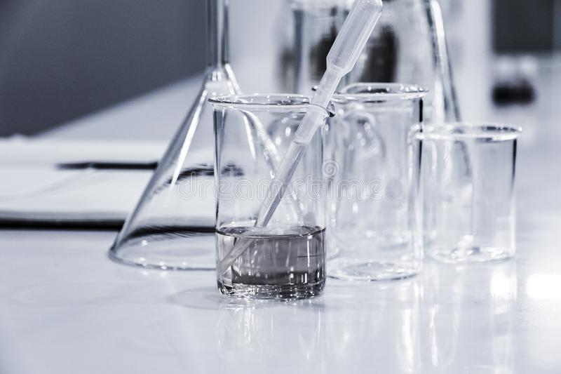 Three clear beakers on white marble tabletop. Three clear beakers placed on white marble tabletop in a chemistry laboratory stock images