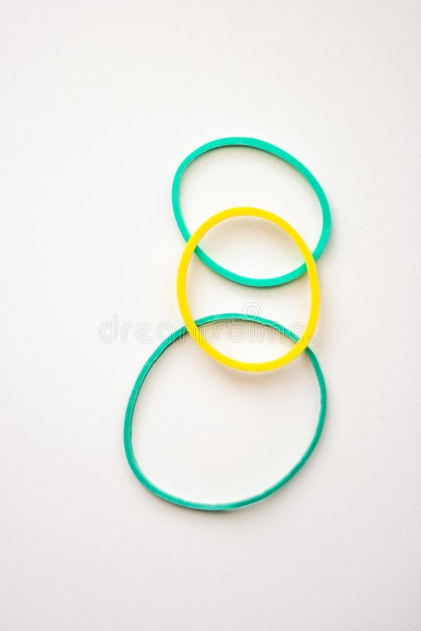Three clerical rubber bands stacked on top of each other stock photo