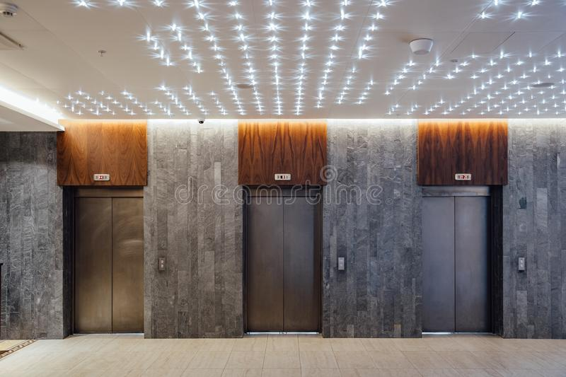 Three closed elevators in modern hotel lobby stock image