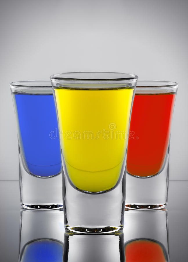 Three cocktails yellow red and blue colors in three wine-gla. Three cocktails yellow red and blue colors in the three wine-glasses with reflection on glass royalty free stock photography