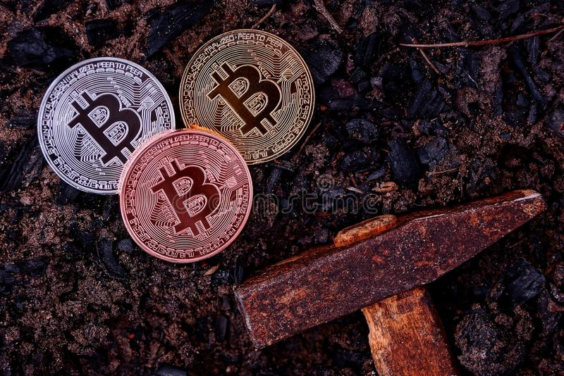 Three coins of bitcoin on black earth and a hammer royalty free stock photo