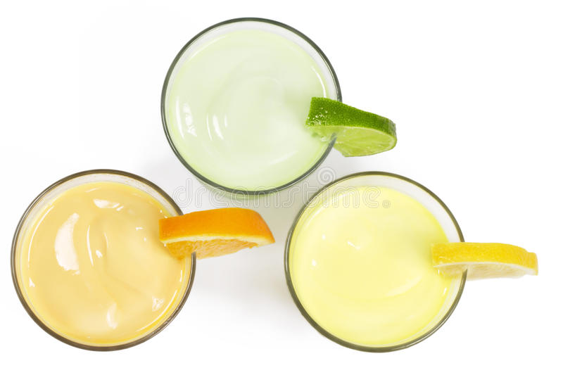 Three cold citrus fruit milkshakes from top. On white background stock image
