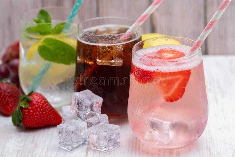 Three cold drinks strawberry, lemon water and cola royalty free stock images