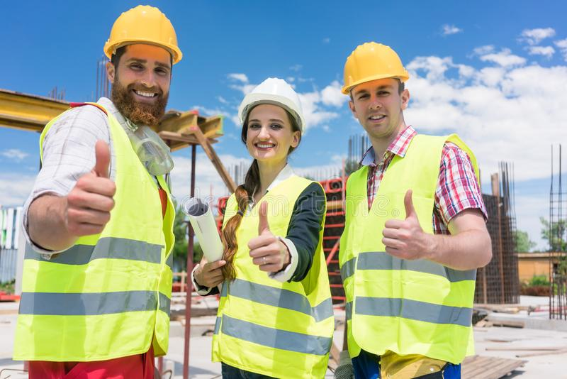 Three colleagues in a construction team showing thumbs up stock photography