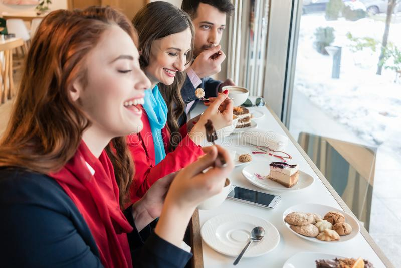 Three colleagues smiling while eating delicious cakes during break. Side view of three young colleagues smiling happy while eating delicious cakes during break stock photography