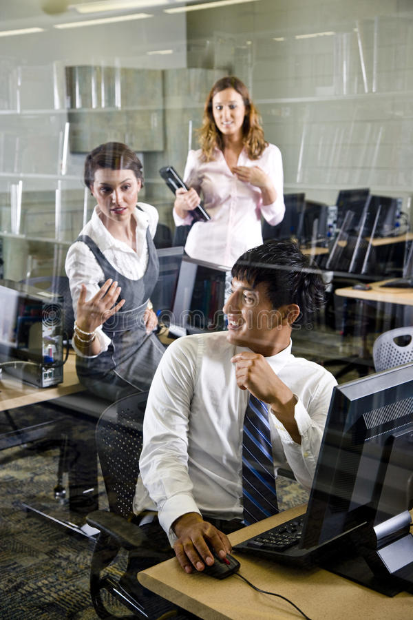 Three college students in library computer room. Three university students conversing in library computer room stock images