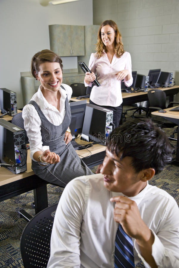Three college students talking in computer lab stock image