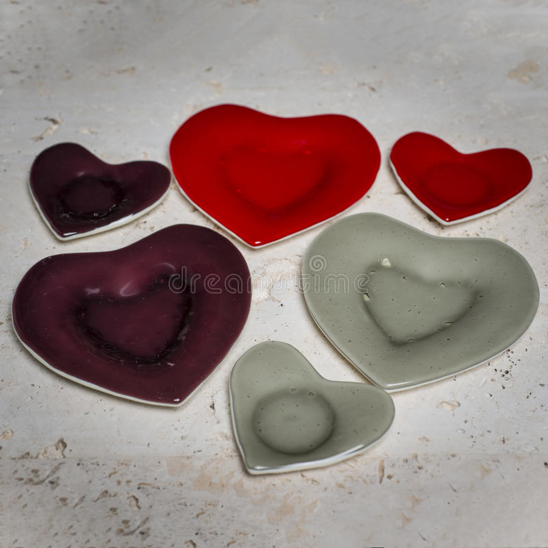 Three Color Matching Heart-Shaped Plate and Saucer Pairs. A collection of three heart-shaped dinner and saucer pairs, one pair colored maroon, one red, and one stock photo