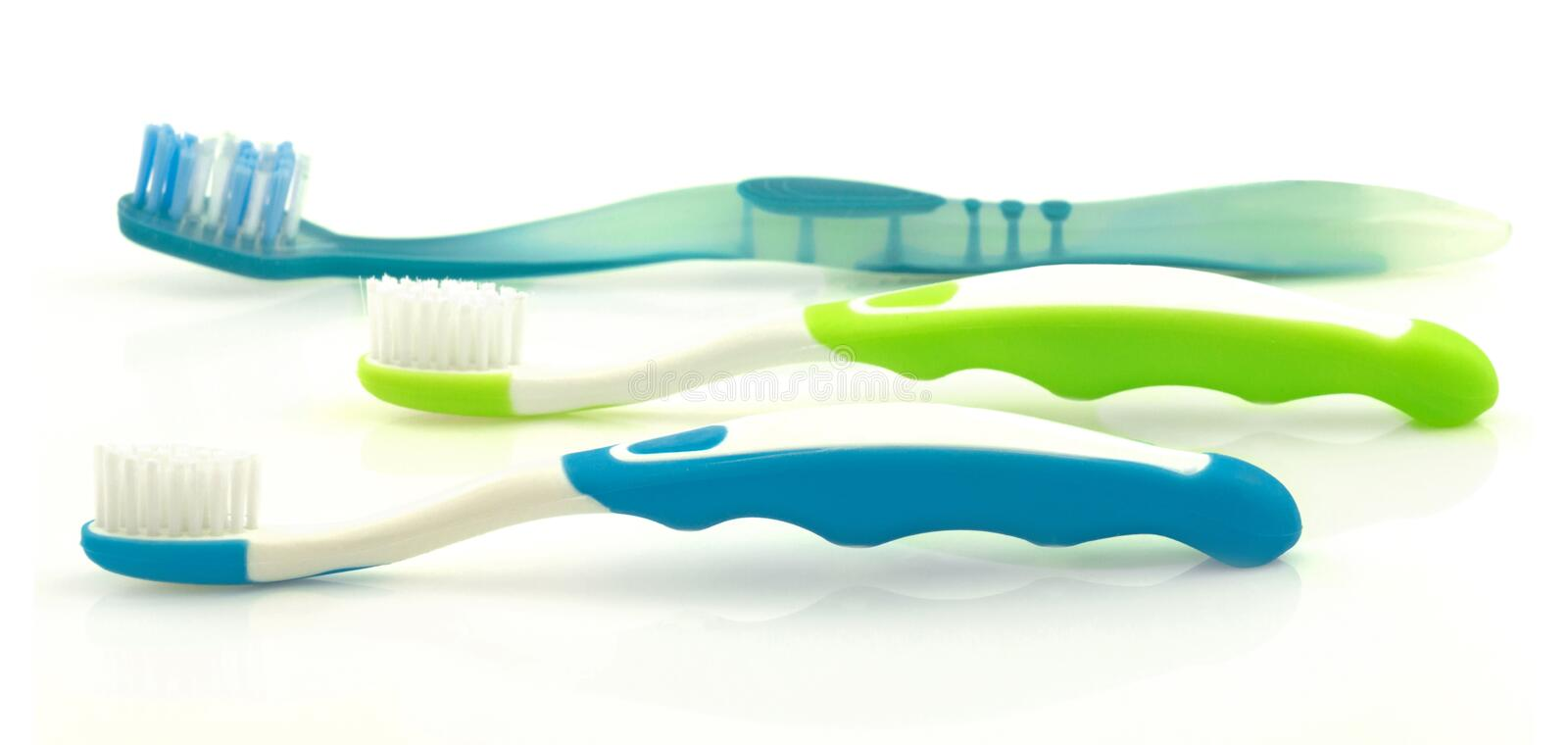 Three color toothbrushes stock photo