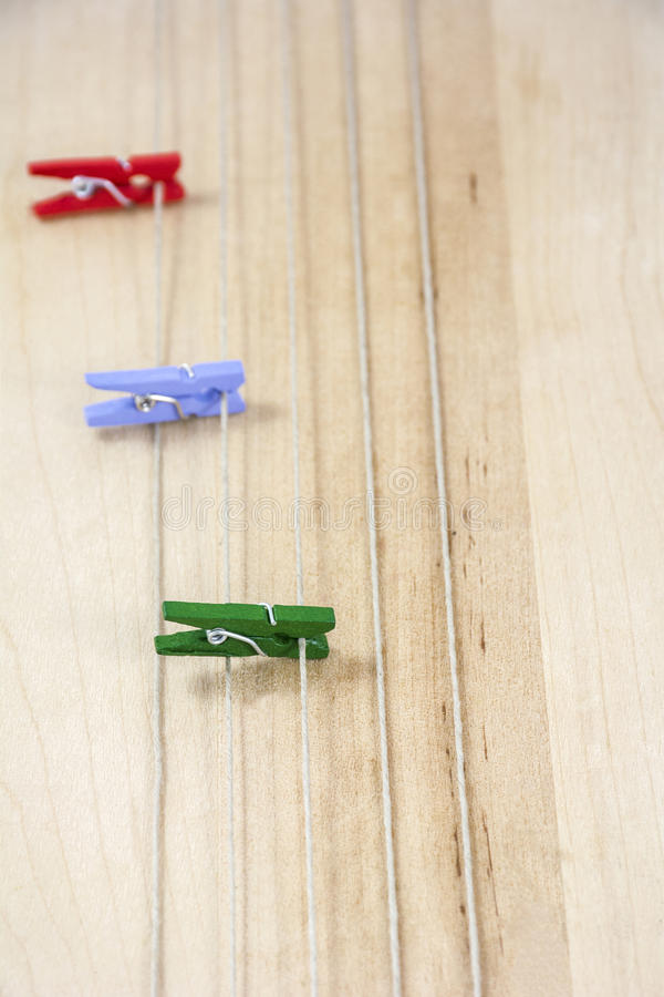 Three colored clothespins on the several ropes. On the wooden background stock photo