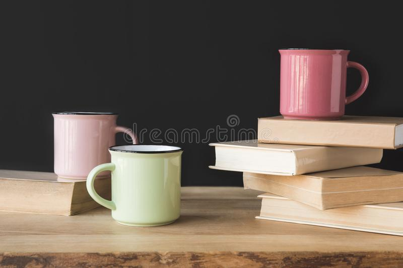 three colored cups and books on wooden table stock images