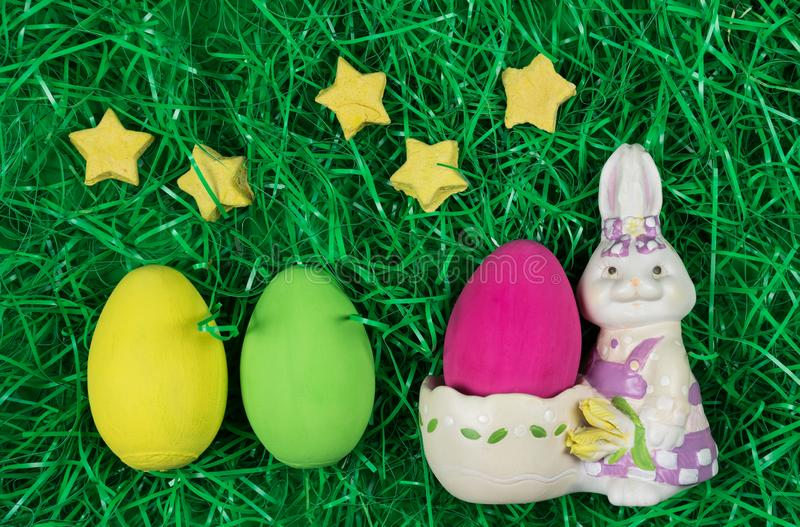 Three colored easter eggs, decorative bunny bowl and stars in green grass. stock photography