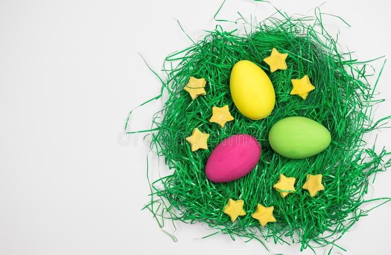 Three colored Easter eggs on decorative green grass with yellow stars on white background. Easter eggs, yellow, pink and green with decorative stars in stock photos