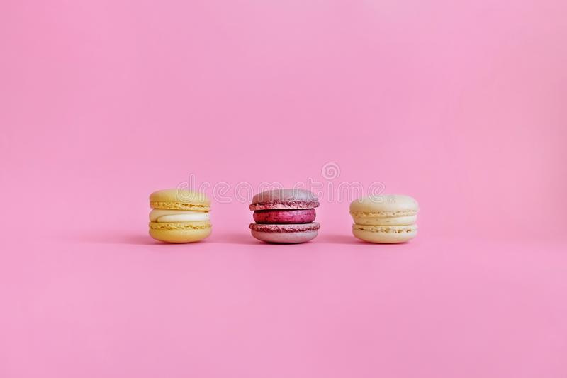 Three colored macaroons on a purple background stock image
