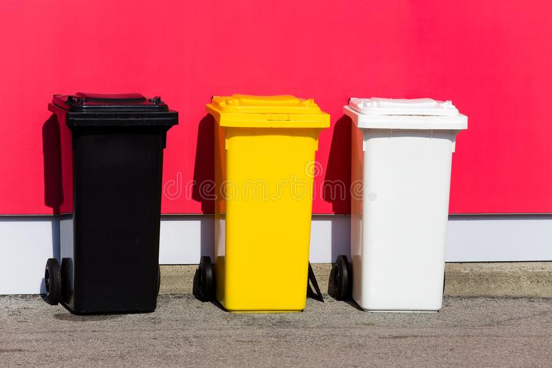 Three colored recycle bins on the street stock photography