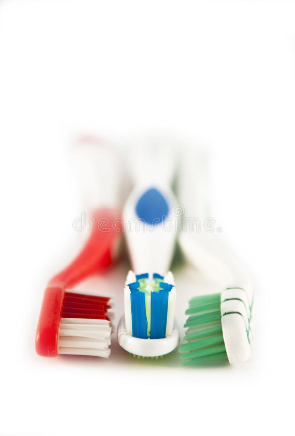 Three colored toothbrushes stock photo