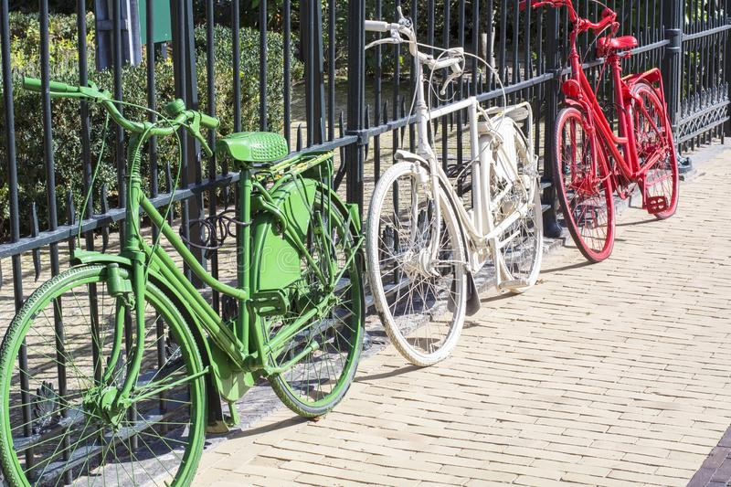 Three colorful bikes - green, white and red - are on the dutch street. In the sunlight stock photography