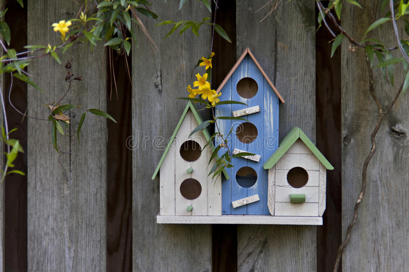 Three colorful birdhouses on wooden fence royalty free stock image