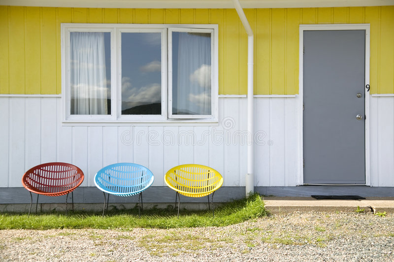 Three Colorful Chairs. A red, blue, and yellow plastic chair in front of a motel on a sunny day stock photos