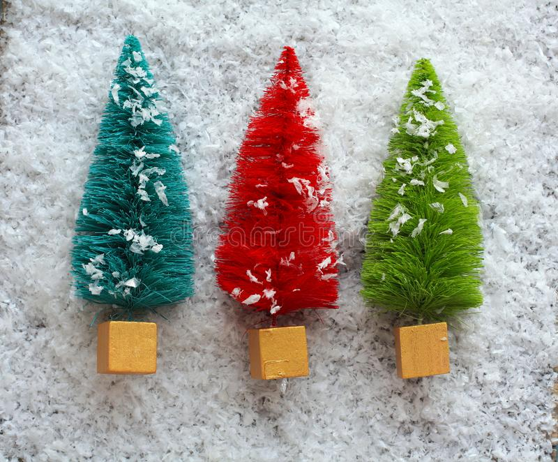 Three colorful Christmas Trees in the snow. Above photograph of three colorful Christmas trees in the snow. All in a row. With snow on a the trees. One blue one stock photos