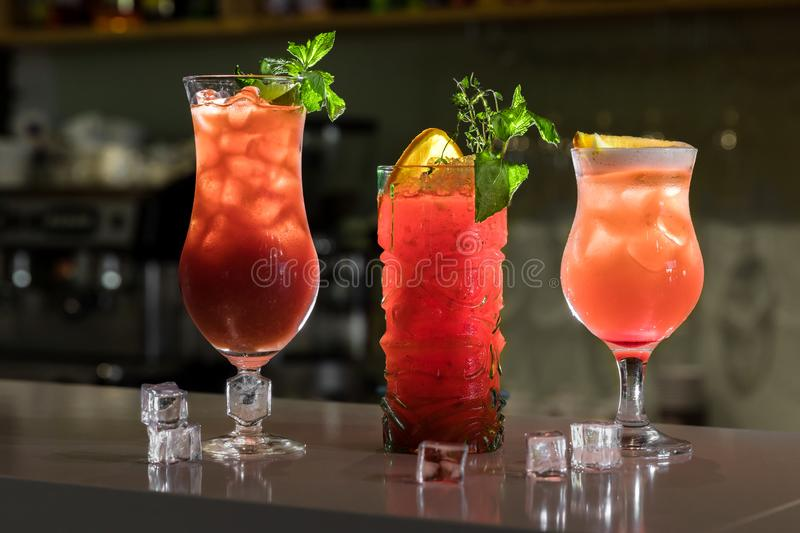 Three colorful cocktails in glasses on bar counter in pub or restaurant on bright blurred background. A lot of ice cubes and mint stock image