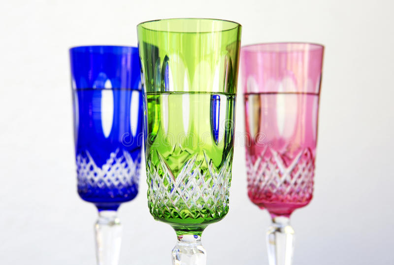 Three colorful crystal glasses on white background royalty free stock image