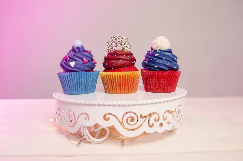 Three colorful delicious cupcakes. On pretty retro white stand stock images