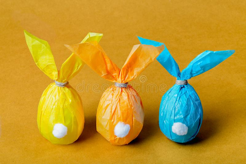 Three colorful Easter eggs in the form of Easter rabbits on a bright background. Three colorful Easter eggs in the form of Easter rabbits on a bright orange stock photography
