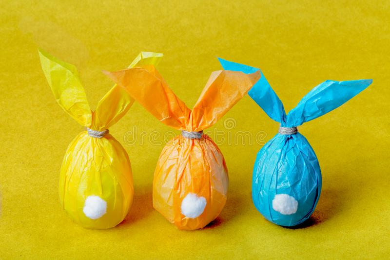 Three colorful Easter eggs in the form of Easter rabbits on a yellow background. Three colorful Easter eggs in the form of Easter rabbits on a bright yellow royalty free stock images