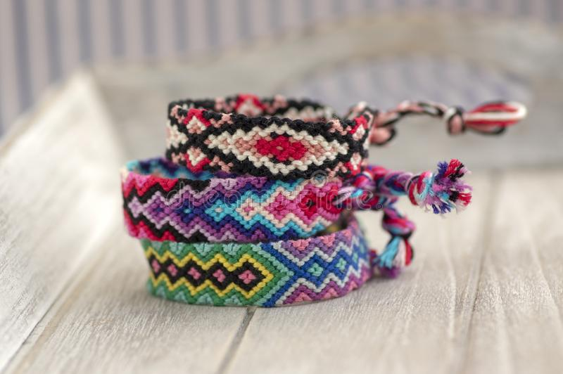 Three colorful handmade homemade natural woven bracelets of friendship on wooden background, rainbow colors, checkered pattern. Bright colors stock photo
