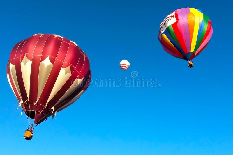 Racing to the Sky 2. Three colorful hot-air balloons float into an early morning blue, blue sky royalty free stock image