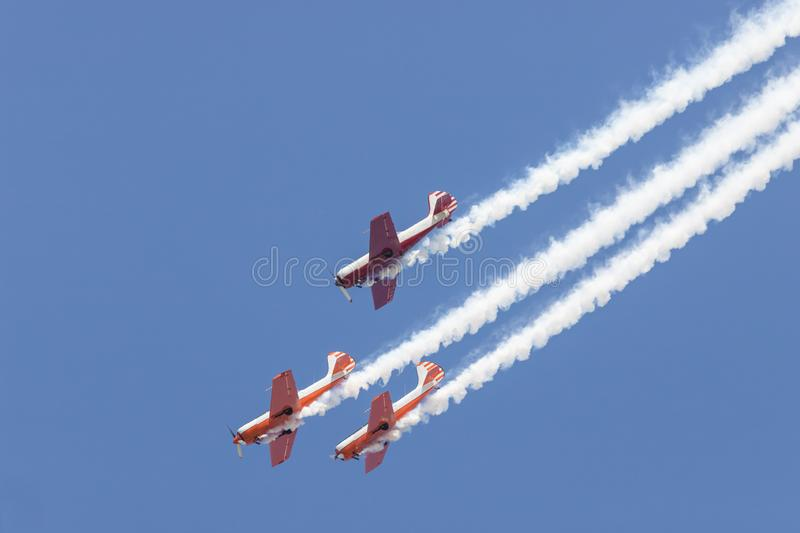 Three colorful jets flying in the sky and performing a show - smoke coming up from the planes stock image