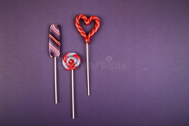 Three colorful lollypops. Three lollypops, striped lollypop looks like an ice-cream, round swirled and hart shaped  on a stick on violet background. Flat lay royalty free stock photography
