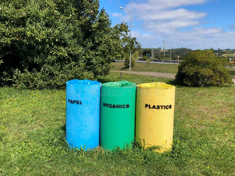 Three colorful outdoor recycling bins with inscriptions in Spanish lenguage. stock photo