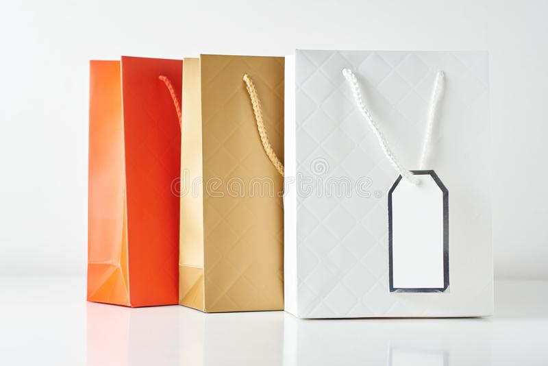 Three colorful paper shopping bag on a white background. Three colorful paper shopping bag on white background, sale, retail, gift, buy, merchandise, consumerism royalty free stock photos
