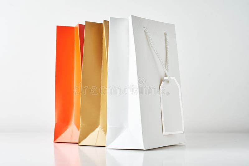 Three colorful paper shopping bag on a white background. Three colorful paper shopping bag on white background, sale, retail, gift, buy, merchandise, consumerism stock image