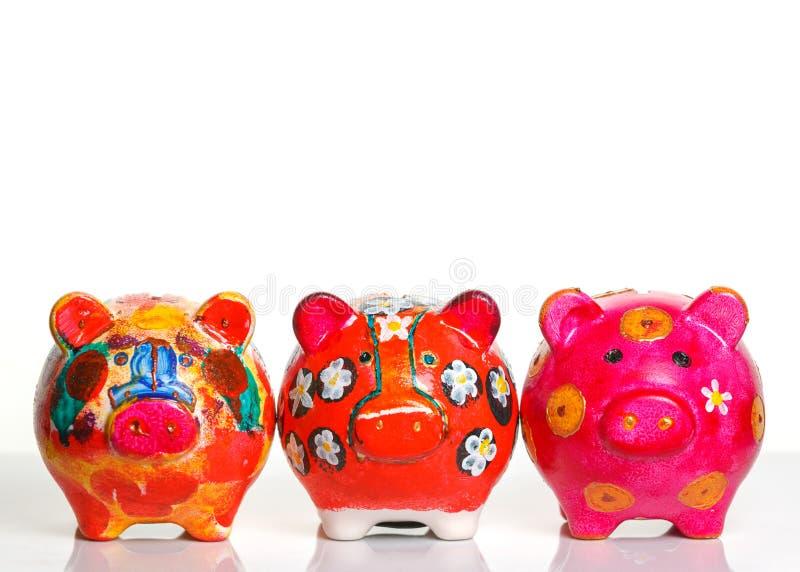 Three colorful piggy banks stock photos