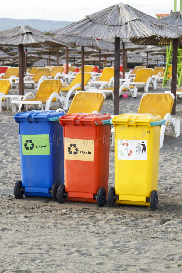 Three colorful recycle bins on the beach. Garbage, recycling, can, trash, plastic, clean, sunbed, deck, chair, container, ecology, concept, waste, disposal royalty free stock images