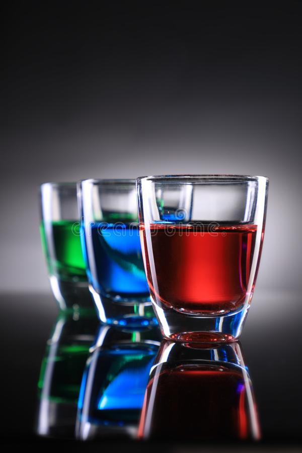 Three Colorful Shot Glasses on Grey Background stock photography