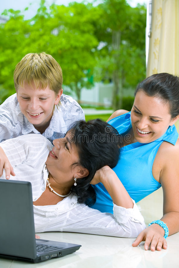 Three and comp. Portrait of happy family getting busy with laptop royalty free stock photos