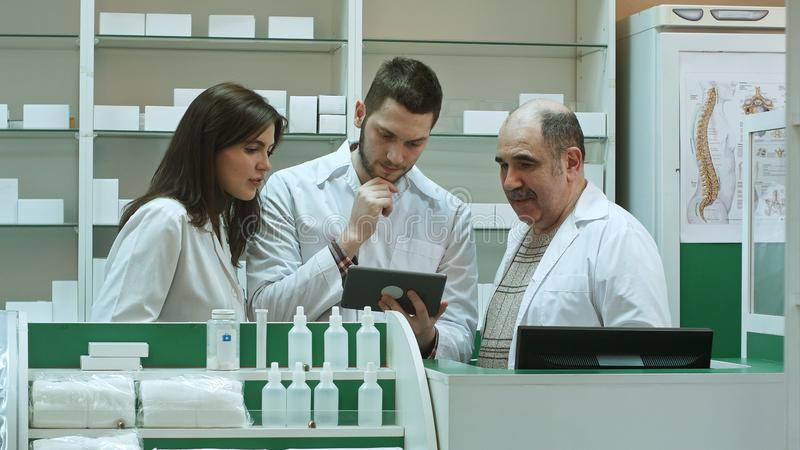 Three concentrated pharmacists using tablet computer at a counter in a pharmacy stock image