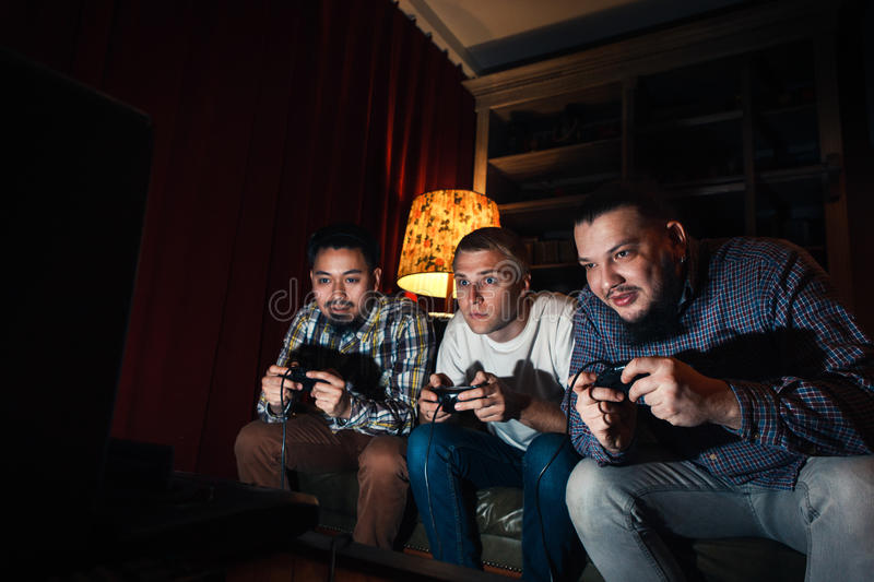 Three concentrated young guy play home video game royalty free stock photo