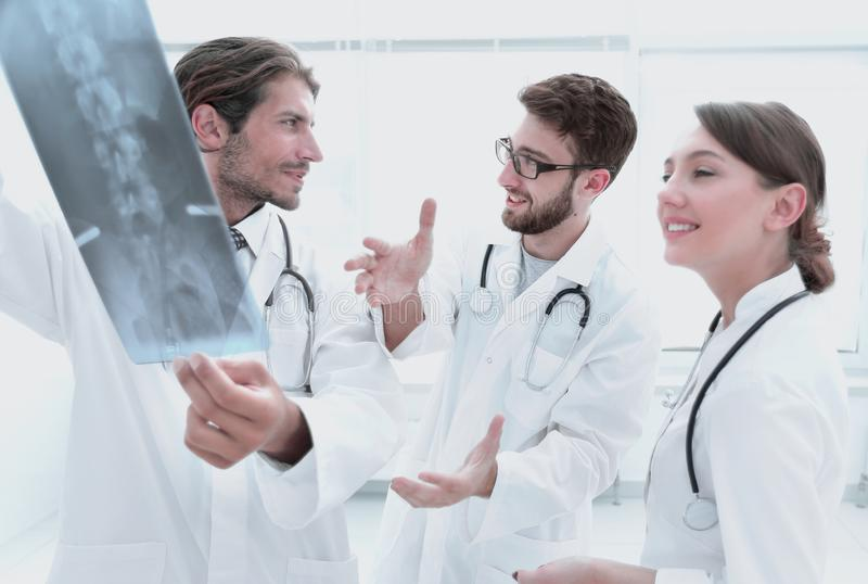 Three confident doctors examine an x-ray. Healthcare, medical and radiology concept - doctors looking at x-ray stock image