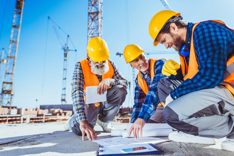 Three construction workers sitting on concrete at construction site, discussing. Building plans royalty free stock image