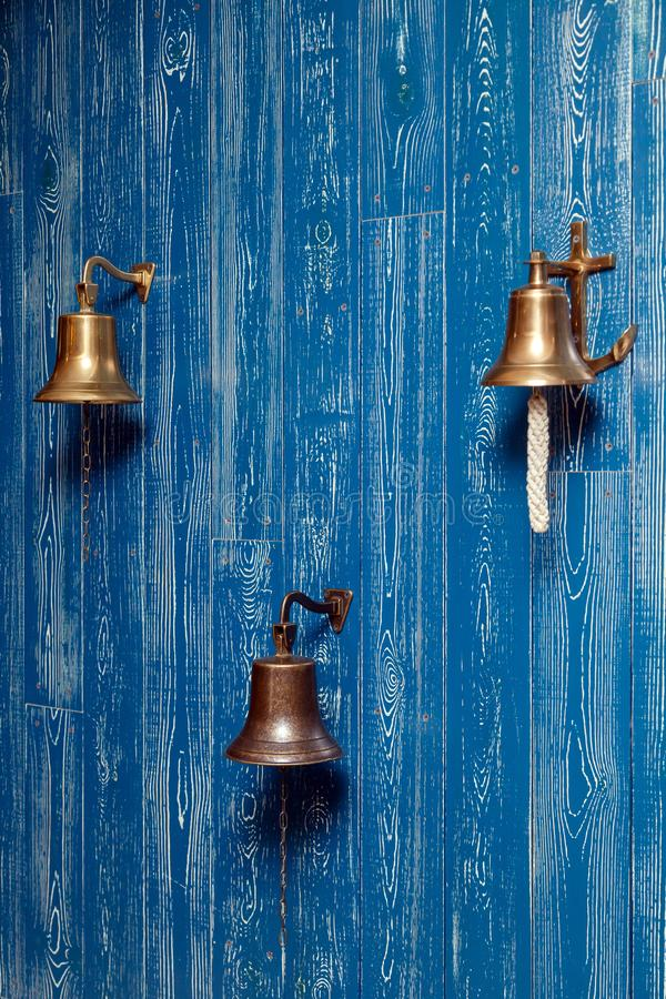 Three copper old vintage bells, doorbell, rope on a wooden blue aged wall. Concept decor element in interior of deck, cabin of royalty free stock photo