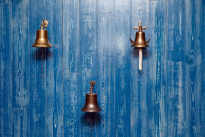Three copper old vintage bells, doorbell, rope on a wooden blue aged wall. Concept decor element in interior of deck, cabin of stock images
