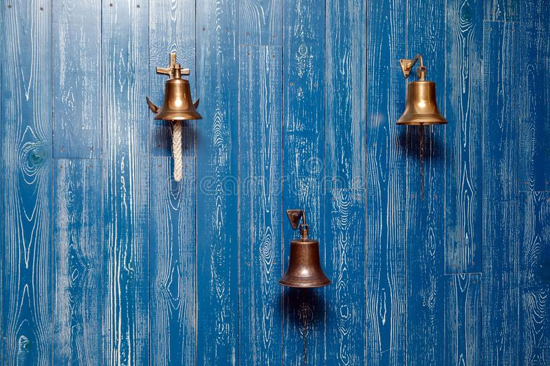 Three copper old vintage bells, doorbell, rope on a wooden blue aged wall. Concept decor element in interior of deck, cabin of royalty free stock image