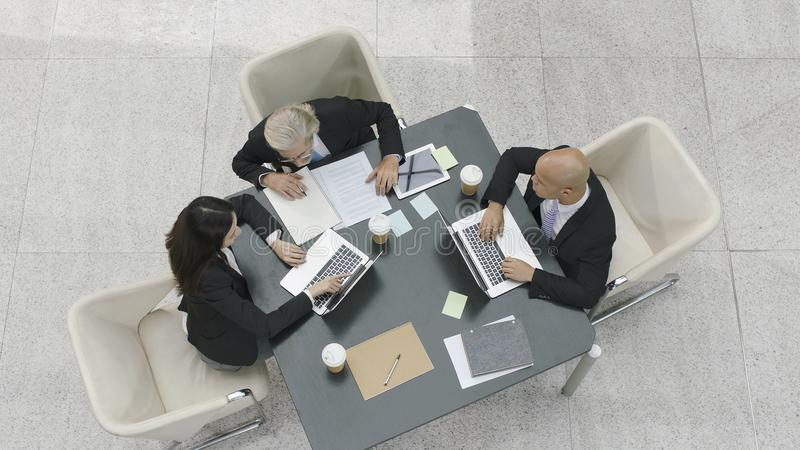 Three corporate executives meeting in office stock photography